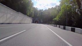 Vista del tunnel della strada con luce gialla scena L'automobile fornisce il tunnul lungo asfaltato semicircolare fatto in montag stock footage