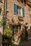 Vista del vicolo con le case e le piante di pietra sotto cielo blu soleggiato in Vence Fotografie Stock Libere da Diritti