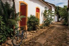 Vista del vicolo del ciottolo con la vecchie casa, vegetazione e bicicletta in Paraty Immagini Stock