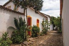 Vista del vicolo del ciottolo con le vecchie case variopinte e della vegetazione in Paraty Fotografie Stock Libere da Diritti