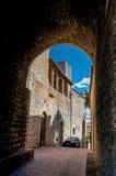 Vista del vicolo, della costruzione di mattone e della torre scuri a San Gimignano Fotografie Stock Libere da Diritti