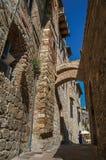 Vista del vicolo stretto con le vecchio costruzioni, arco e la donna camminanti a San Gimignano Immagini Stock