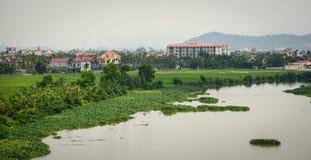 Vista del villaggio con il fiume, erba verde, cielo nuvoloso Immagine Stock Libera da Diritti
