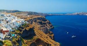 Vista del villaggio di Fira sviluppata sopra la scogliera del vulcano e l'isola blu di Santorini del mare, Grecia fotografie stock libere da diritti