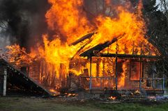 Vista delantera ardiendo de llamas de la casa de la vista lateral foto de archivo libre de regalías