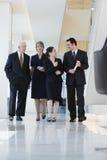 Vista delantera de cuatro ejecutivos que recorren en pasillo. Fotografía de archivo libre de regalías