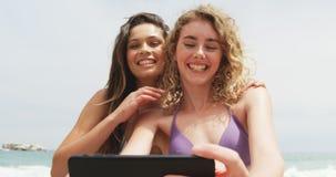 Vista delantera de dos amigos femeninos de la raza mixta que toman el selfie con el tel?fono m?vil en la playa 4k almacen de video