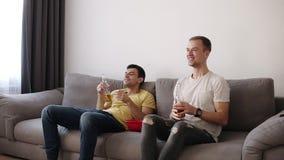 Vista delantera de dos compañeros de cuarto, amigos que miran fútbol en la TV que se sienta en un sofá cómodo en la sala de estar metrajes