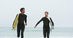 Vista delantera de dos personas que practica surf de sexo masculino que corren así como la tabla hawaiana en la playa 4k metrajes