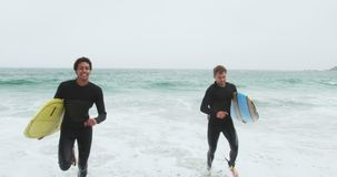 Vista delantera de dos personas que practica surf de sexo masculino que corren as? como la tabla hawaiana en la playa 4k almacen de video