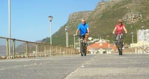 Vista delantera de la bicicleta que monta de los pares caucásicos mayores activos en una 'promenade' en la playa 4k metrajes