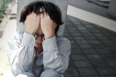 Vista delantera de la cara asiática joven deprimida triste de la cubierta del hombre de negocios con las manos Imagen de archivo
