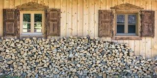 Vista delantera de la casa de madera del chalet con la pila de madera Foto de archivo