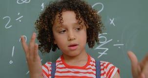 Vista delantera de la colegiala de la raza mixta que cuenta con su finger contra la pizarra en la sala de clase 4k almacen de metraje de vídeo