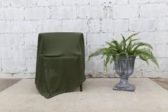 Vista delantera de la cubierta verde del paño la silla de madera con la pared y el florero del cemento imágenes de archivo libres de regalías