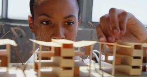 Vista delantera de la empresaria afroamericana que mira el modelo arquitectónico en una oficina moderna 4k almacen de video
