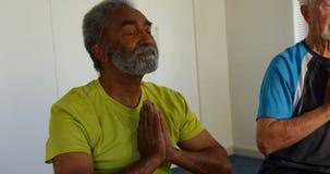 Vista delantera de la gente mayor de la raza mixta activa que realiza yoga en el estudio 4k de la aptitud metrajes