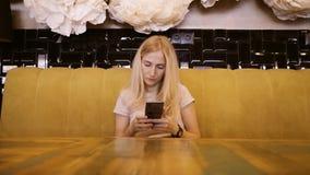 Vista delantera de la hembra joven hermosa que usa su teléfono móvil en café Mujer que usa el app en smartphone en el café que es metrajes
