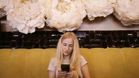 Vista delantera de la hembra joven hermosa que usa su teléfono móvil en café Mujer que usa el app en smartphone en el café que es almacen de video