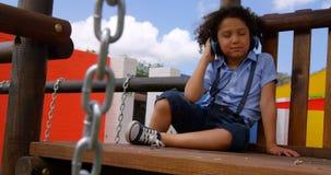 Vista delantera de la música que escucha de la colegiala de la raza mixta en los auriculares en el patio 4k de la escuela metrajes