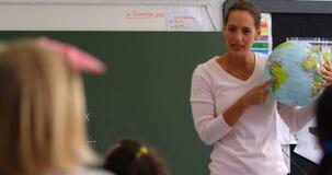 Vista delantera de la maestra caucásica que explica sobre el globo en la sala de clase 4k almacen de video