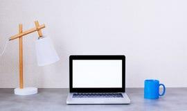 Vista delantera de la mesa con el ordenador port?til en blanco y de art?culos decorativos en fondo de la pared imagenes de archivo