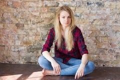 Vista delantera de la muchacha blanca atractiva que se sienta en piso de madera Fotografía de archivo