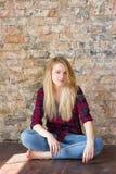 Vista delantera de la muchacha blanca atractiva que se sienta en piso de madera Foto de archivo