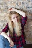 Vista delantera de la muchacha blanca atractiva que se sienta en piso de madera Fotografía de archivo libre de regalías