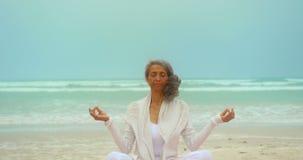 Vista delantera de la mujer afroamericana mayor activa que hace yoga en la estera del ejercicio en la playa 4k almacen de video