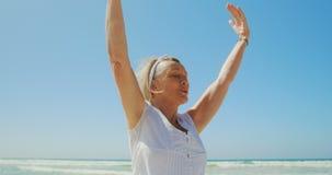 Vista delantera de la mujer caucásica mayor activa que realiza yoga en la playa 4k almacen de metraje de vídeo