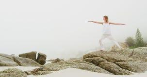 Vista delantera de la mujer caucásica que realiza yoga en la playa 4k almacen de metraje de vídeo