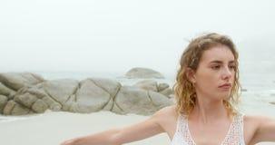Vista delantera de la mujer cauc?sica que realiza yoga en la playa 4k metrajes