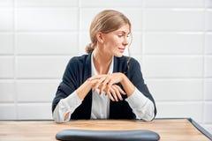 Vista delantera de la mujer elegante que mira el lado y que muestra la nueva manicura imagen de archivo