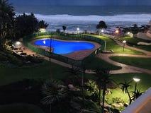 Vista delantera de la playa de una piscina y de un océano imágenes de archivo libres de regalías