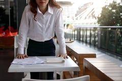 Vista delantera de la situación asiática joven subrayada y del destrozo de la mujer de negocios en el escritorio con sus manos en Foto de archivo
