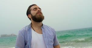 Vista delantera de la situación caucásica del hombre con el ojo cerrado en la playa 4k almacen de metraje de vídeo