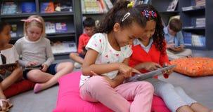Vista delantera de las colegialas de la raza mixta que estudian en la tableta digital en la biblioteca escolar 4k metrajes