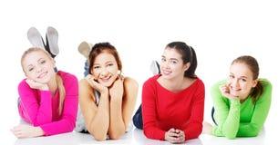 Vista delantera de las muchachas adolescentes sonrientes felices que mienten en su panza Imagen de archivo