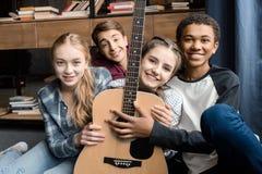 Vista delantera de los adolescentes felices que sostienen la guitarra en casa, Fotos de archivo libres de regalías