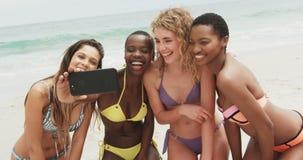 Vista delantera de los amigos femeninos de la raza mixta que toman el selfie con el teléfono móvil en la playa 4k metrajes