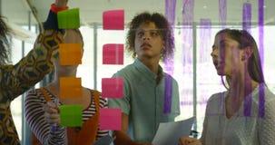 Vista delantera de los ejecutivos de operaciones jovenes de la raza mixta que trabajan en notas pegajosas en la oficina moderna 4 almacen de metraje de vídeo