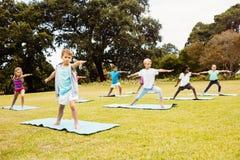 Vista delantera de los niños que hacen yoga Foto de archivo libre de regalías