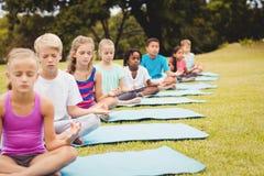 Vista delantera de los niños que hacen yoga Foto de archivo