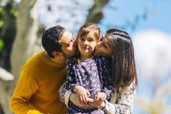 Vista delantera de los padres felices que besan a su hija preciosa al aire libre en el parque en un d?a soleado imagenes de archivo
