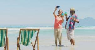 Vista delantera de los pares afroamericanos mayores activos que toman el selfie con el teléfono móvil en la playa 4k almacen de video