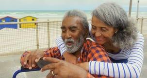 Vista delantera de los pares afroamericanos mayores activos que toman el selfie con el teléfono móvil en la 'promenade' 4k almacen de metraje de vídeo