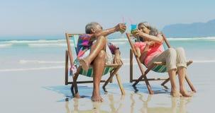 Vista delantera de los pares afroamericanos mayores activos que tuestan bebidas en deckchair en la playa 4k almacen de metraje de vídeo