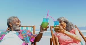 Vista delantera de los pares afroamericanos mayores activos que tuestan bebidas en deckchair en la playa 4k metrajes