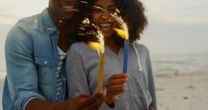 Vista delantera de los pares afroamericanos que sostienen bengalas en manos en la playa 4k metrajes